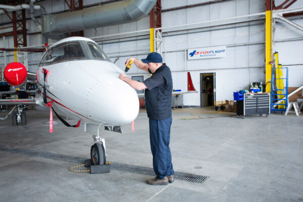 Maintenance Team Working on Learjet front